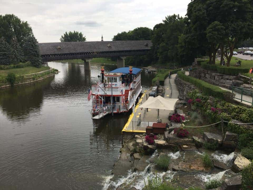 A boat traveling along a river next to a body of water. The Bavarian Inn Summertime Edition