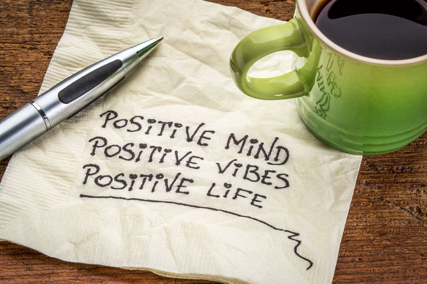 "Morning coffee on top of napkin that reads, ""Positive mind, positive vibes, positive life.\"""