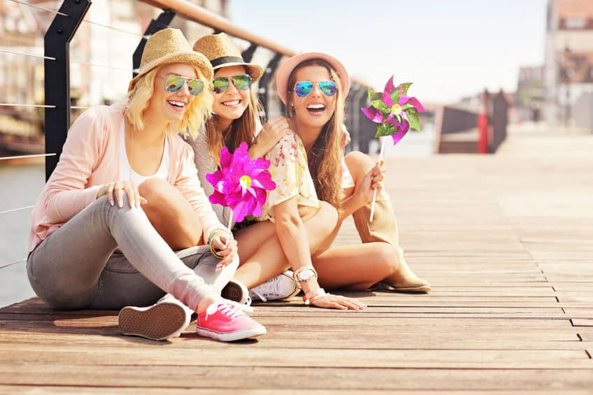 A group of women who are sitting on a boardwalk, happy and being social.