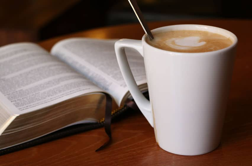 Cup of coffee and open book.