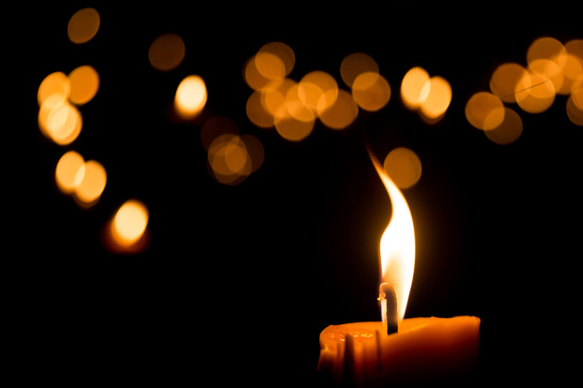 Candle burning brightly in the darkness.