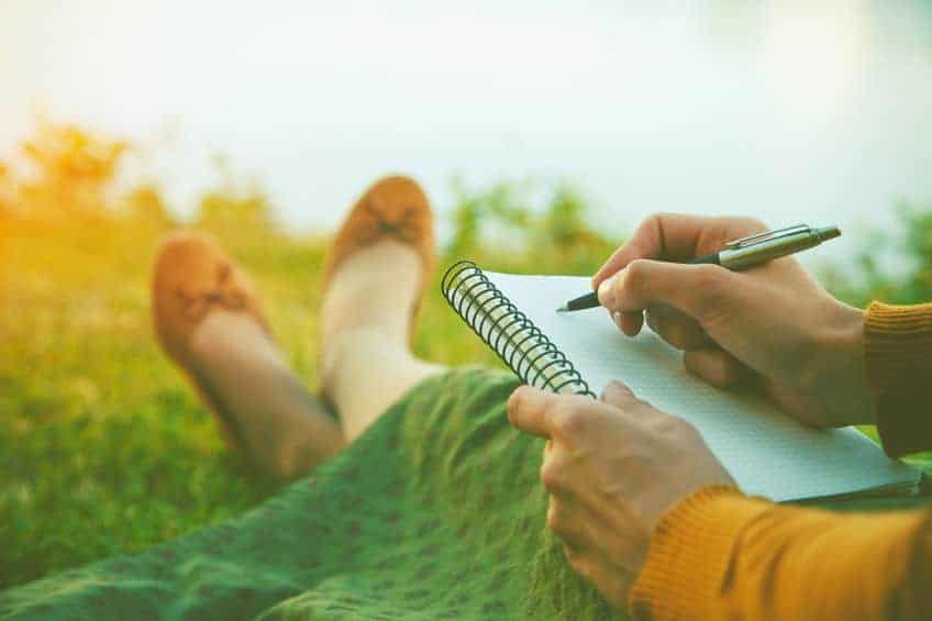 Woman sitting in the grass and writing in her journal.