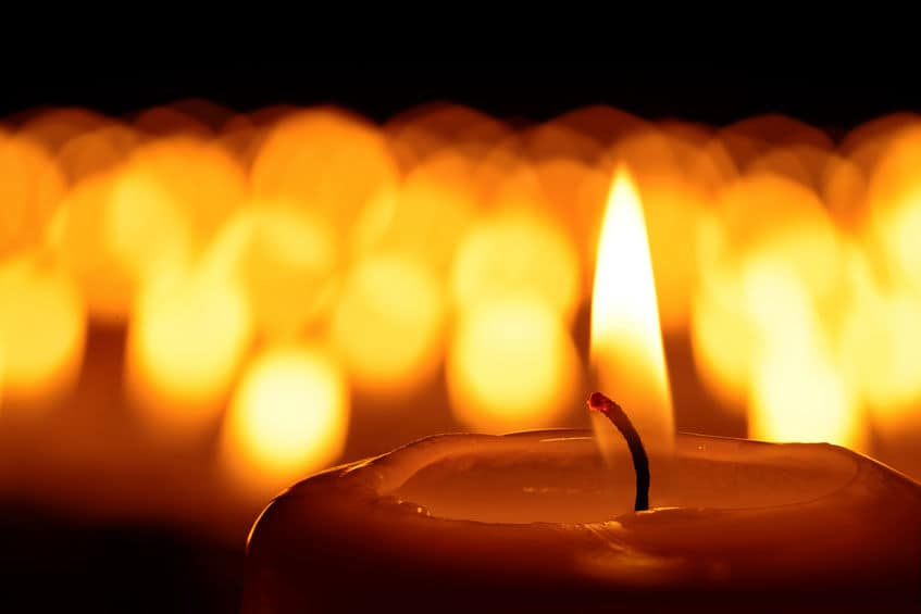 Candle burning against a dark background.