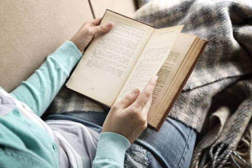 Woman reading book, while wrapped in a blanket.
