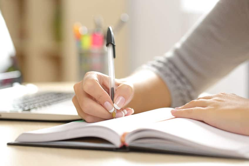 Woman writing thoughts and personal feelings in notebook.