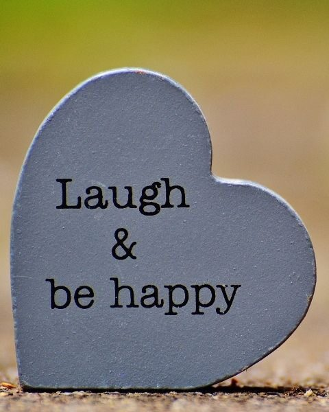 a heart shaped wooden plaque that says Laugh & Be Happy