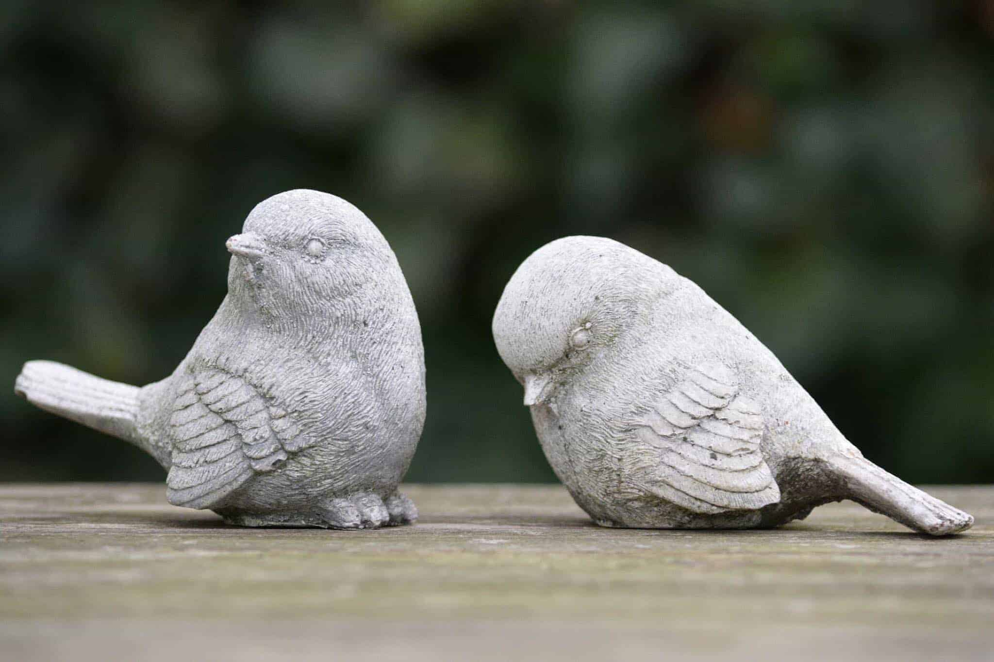 Two bird statues, one is looking up and the other is looking down.