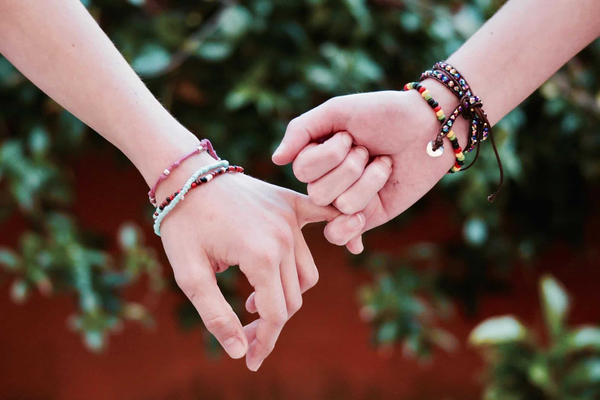 Two people interlocking fingers together in encouragement and kindness.
