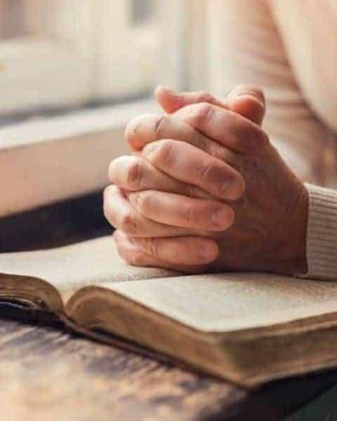 a person with their hands clasped together in a praying way on top of an open book in front of a window