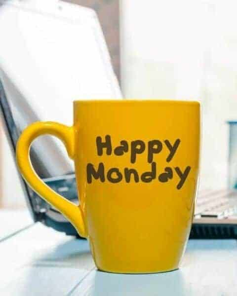 a yellow mug that says Happy Monday on it, in front of a laptop