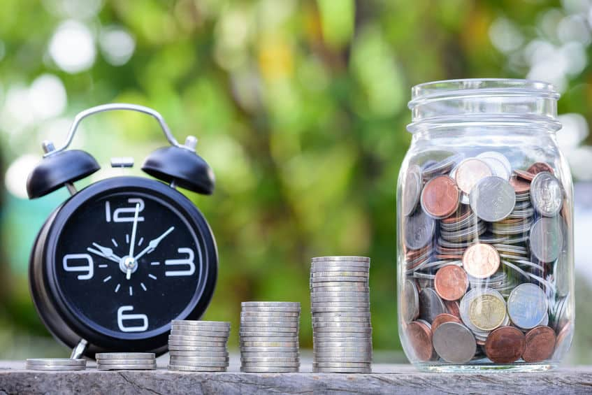 Alarm clock by a stack of coins and a jar full of money. How to save money by meal planning.