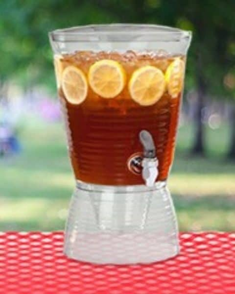 gallon drink dispenser filled with iced tea and lemon slices on a table with a red tablecloth outside.
