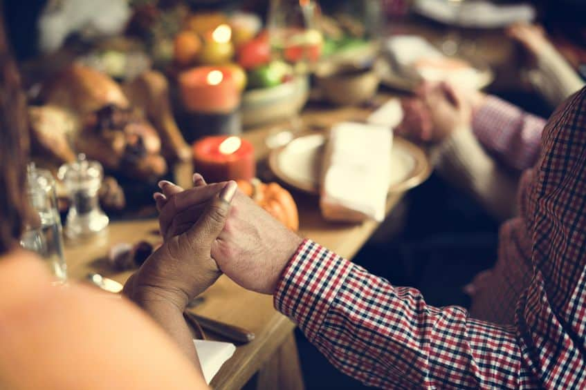 Thanksgiving family holding hands in prayer.