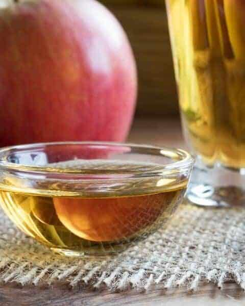 a bowl of apple cider vinegar sitting on a table with some apples nearby