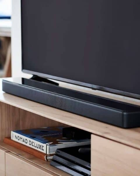 Bose sound bar sitting in front of a flat screen TV on a TV stand