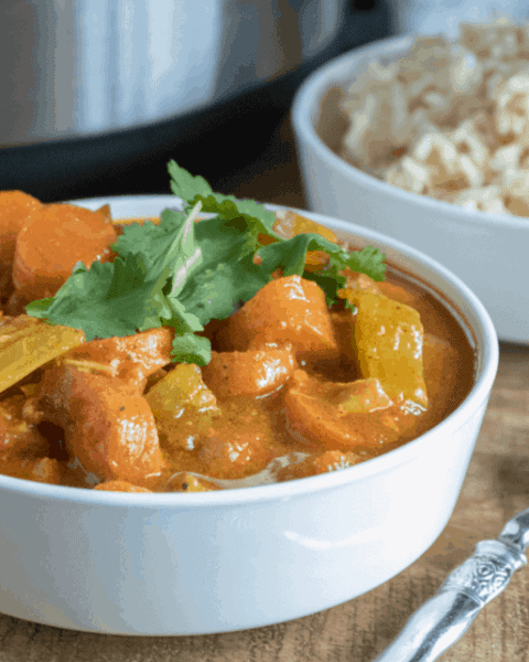 A bowl of food on a table, with Chicken and Curry
