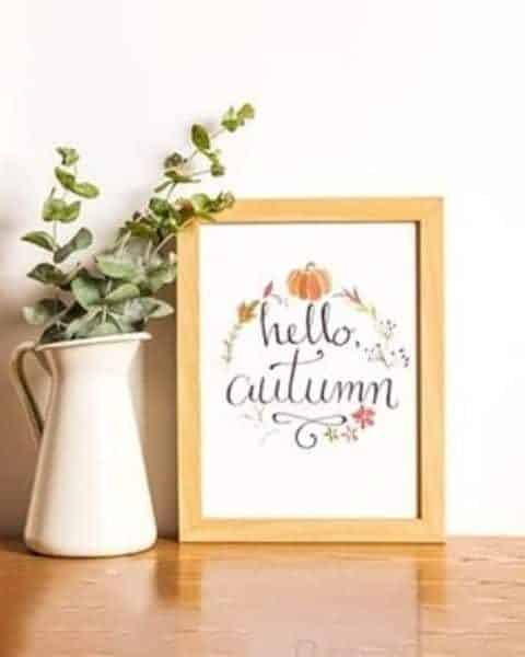 hello automn framed sign sitting ona wooden table next to a pitcher of flowers