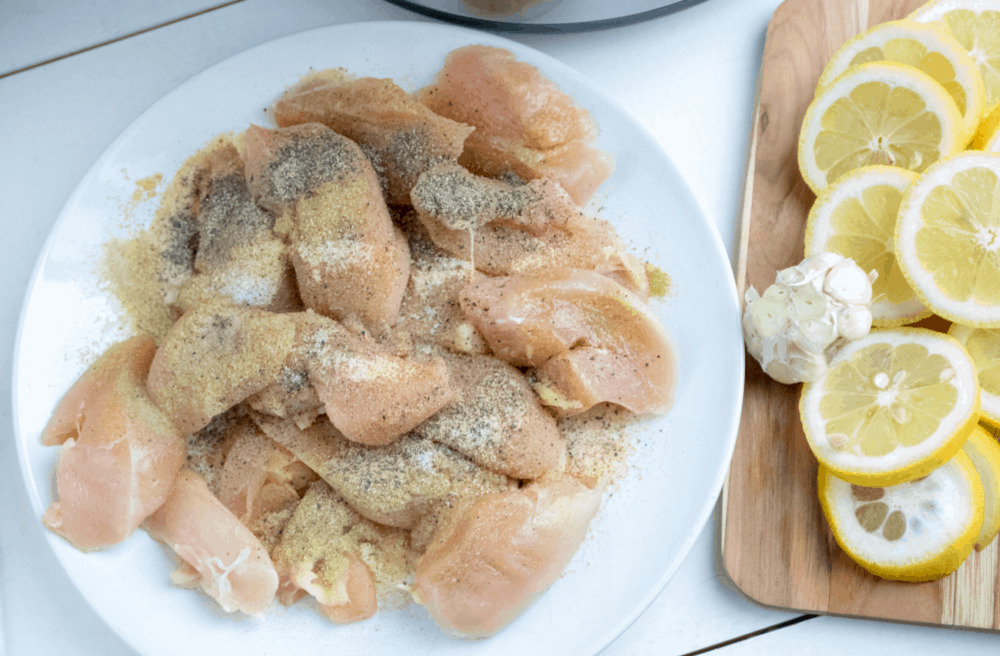 Raw chicken with seasonings and lemon.