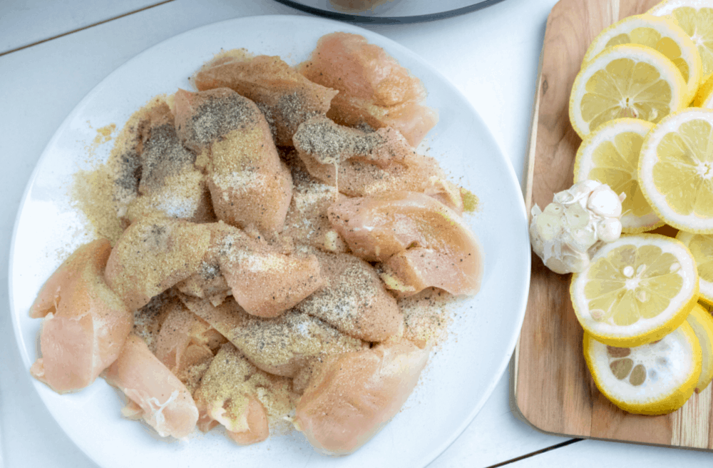 Raw chicken with seasonings and lemon.