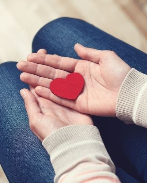 a woman holding a red paper heart in her hands