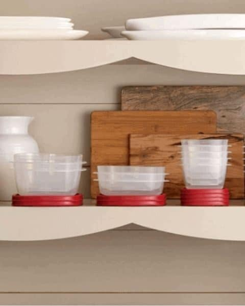Rubbermaid containers stacked in a cupboards with a pitcher and several wooden cutting boards