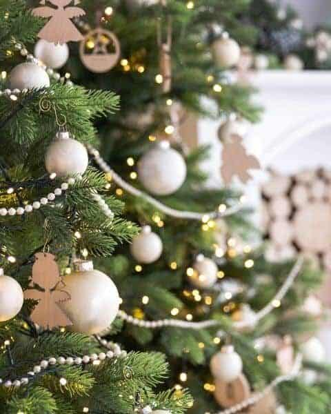Christmas tree decorated in white lights and bulbs with beaded garland