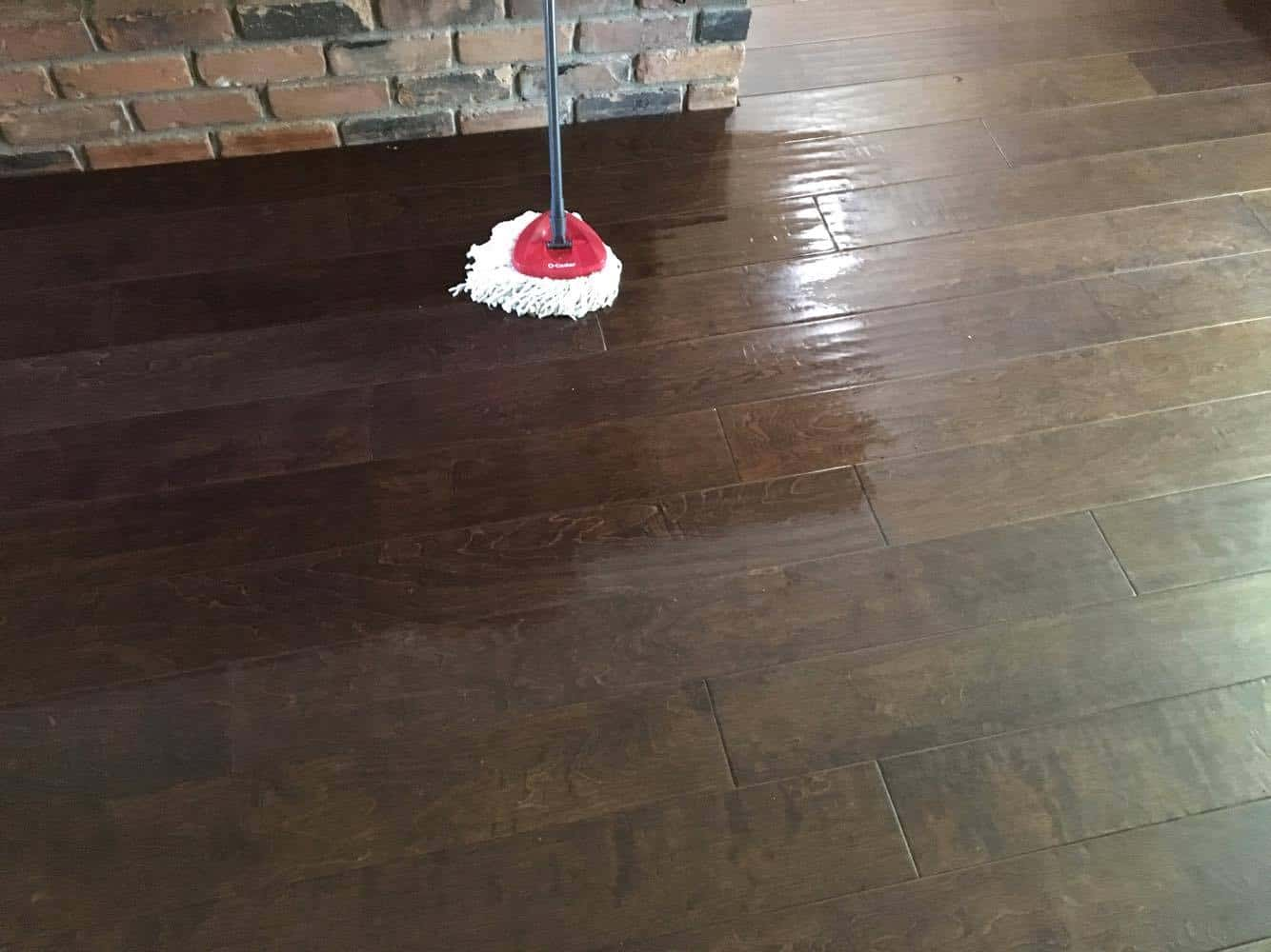 Mop cleaning wooden floor with homemade cleaning supplies.