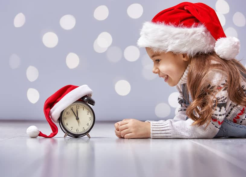 Little girl in front of alarm clock while wearing a Santa hat. The Best Frugal or Free Christmas Gifts for Kids