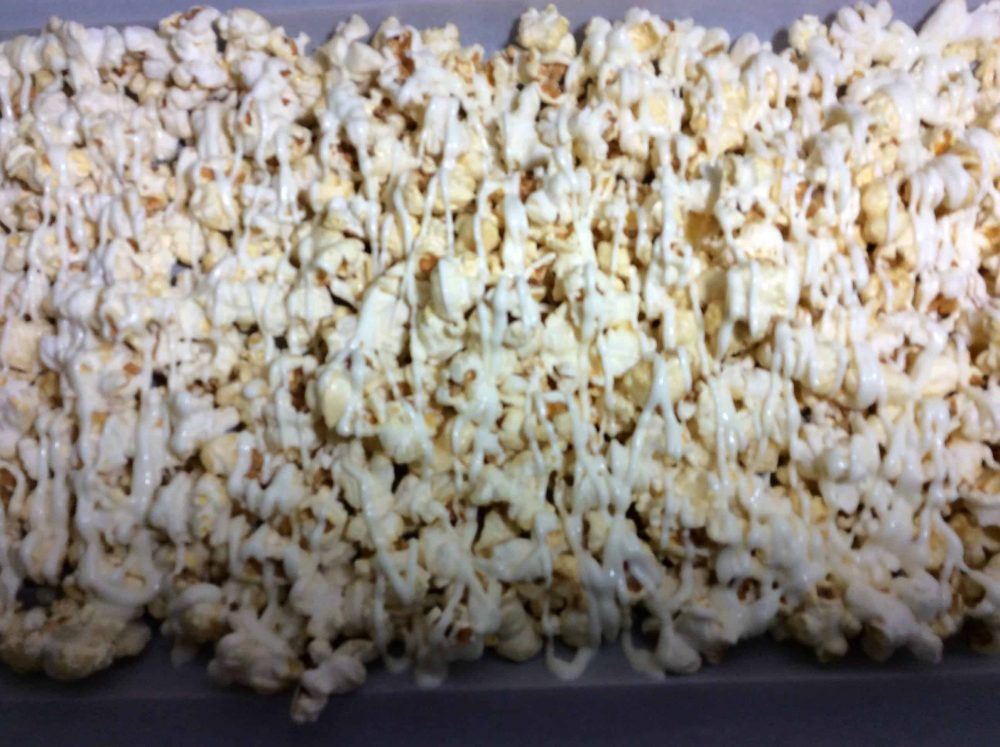 Drizzle the popcorn with white chocolate.