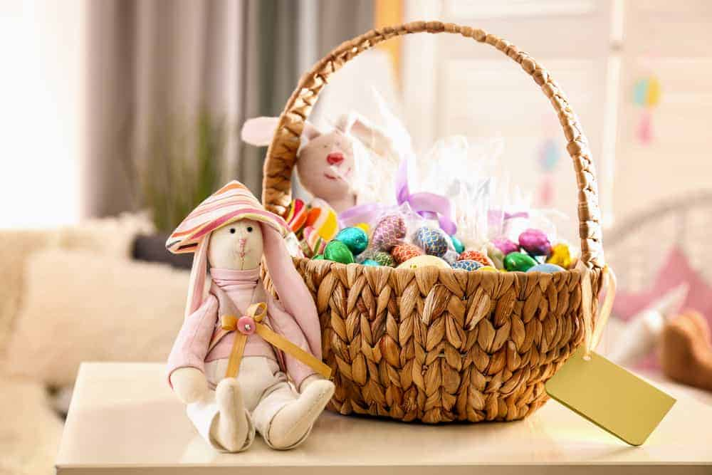 Beautiful Easter basket with traditional decorations and sweets near cute rabbit toy on table in light room