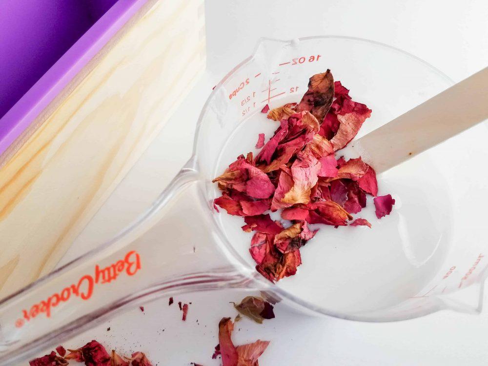 Add dried flower petals into the Botanical Goat Milk Handmade Soap mixture.