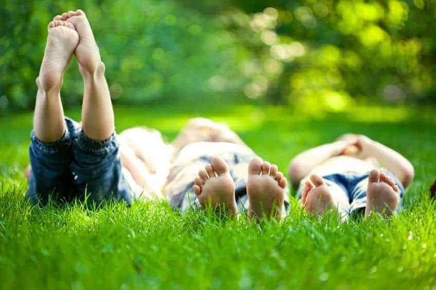 A small group of children laying on the green grass laughing and talking with each other.