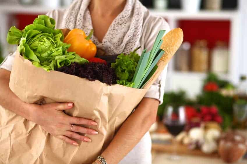 woman holding a bag of healthy groceries.