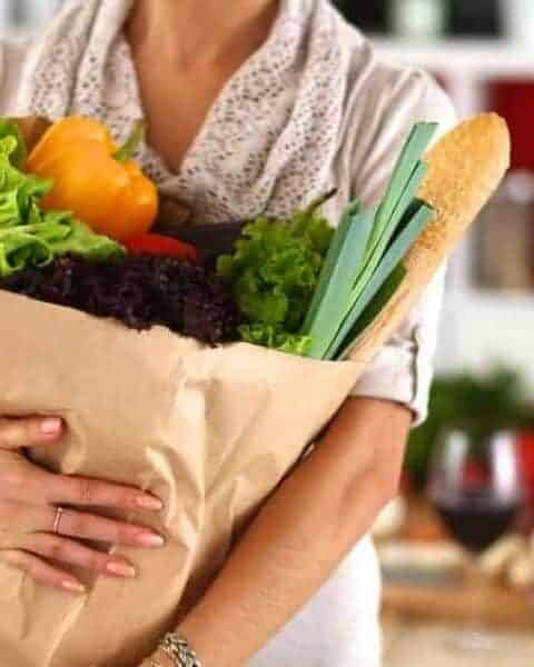 woman holding a paper bag filled with fresh produce