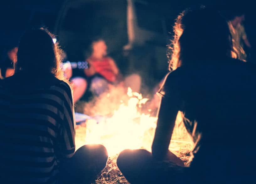 A couple of people standing around a fire. Camping Trips Can Make Fun Frugal Summer Vacations