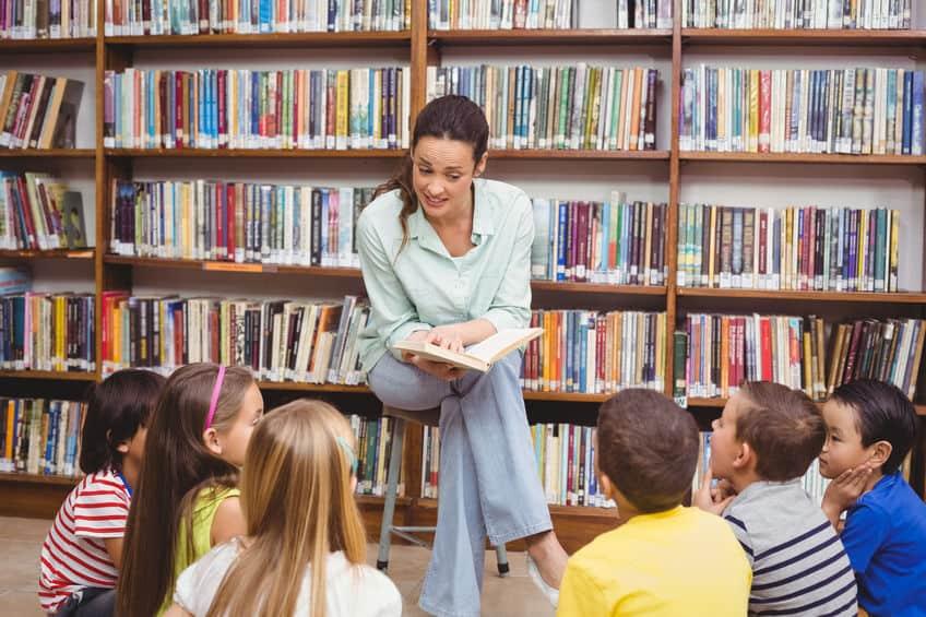 Librarian reading books for children\'s story time program.