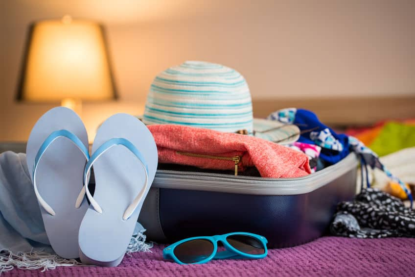 Summer hat, sandals, clothes, and sunglasses packed in a suitcase.