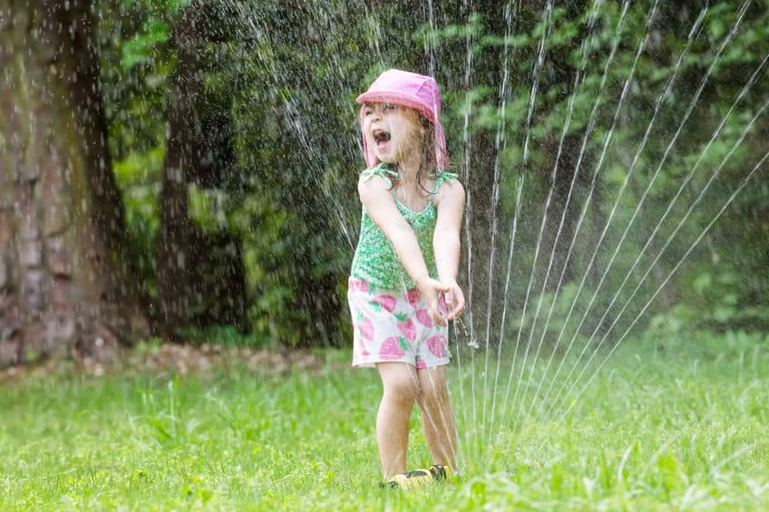 Girl playing in the sprinklers.