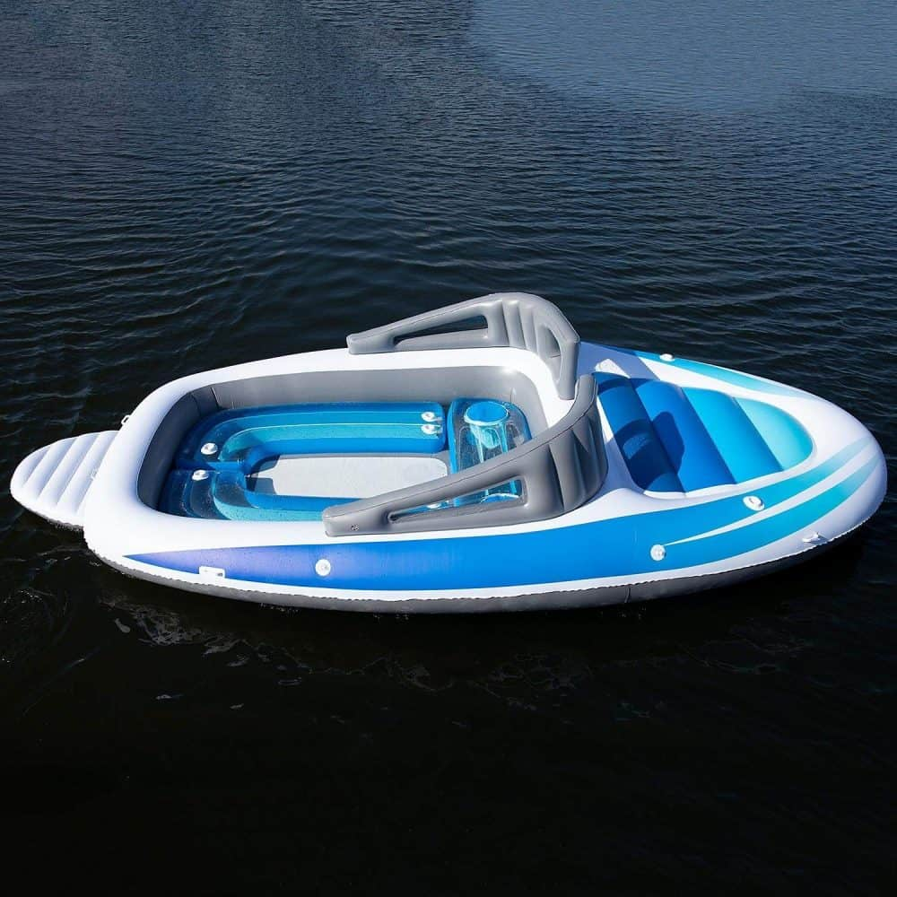 A blue and white boat sitting next to a body of water.  Life-size Inflatable Speed Boat