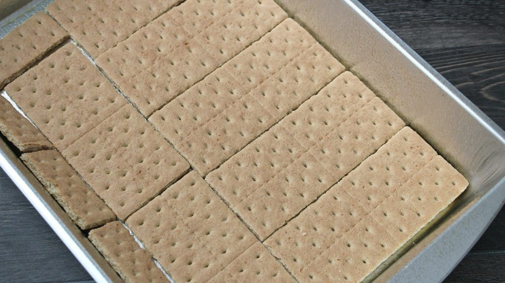 adding the graham cracker crust to the bottom of the pan