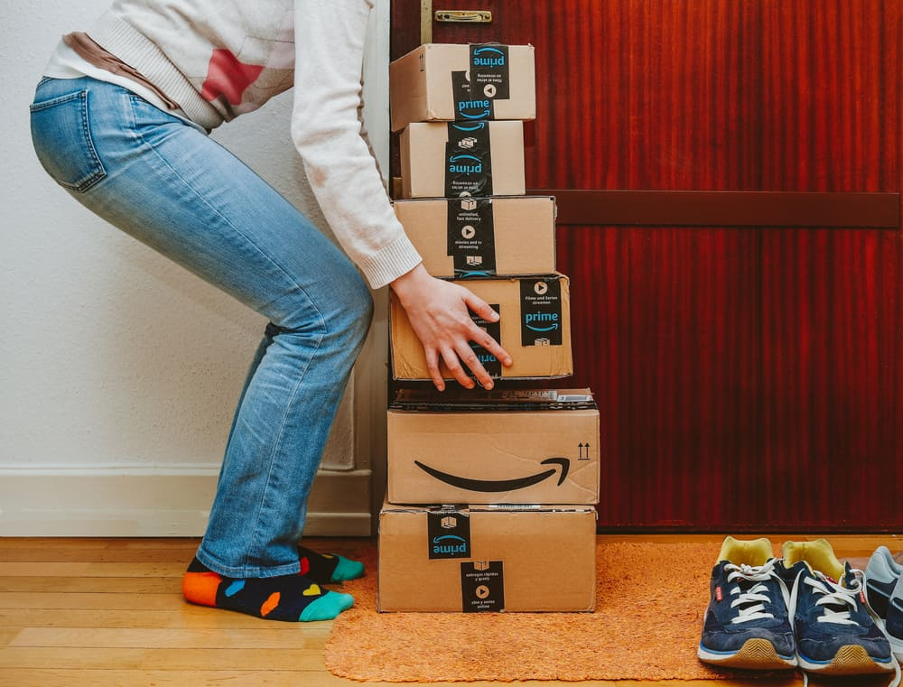 Woman lifting heavy stack of Amazon Prime packages delivered to a home door
