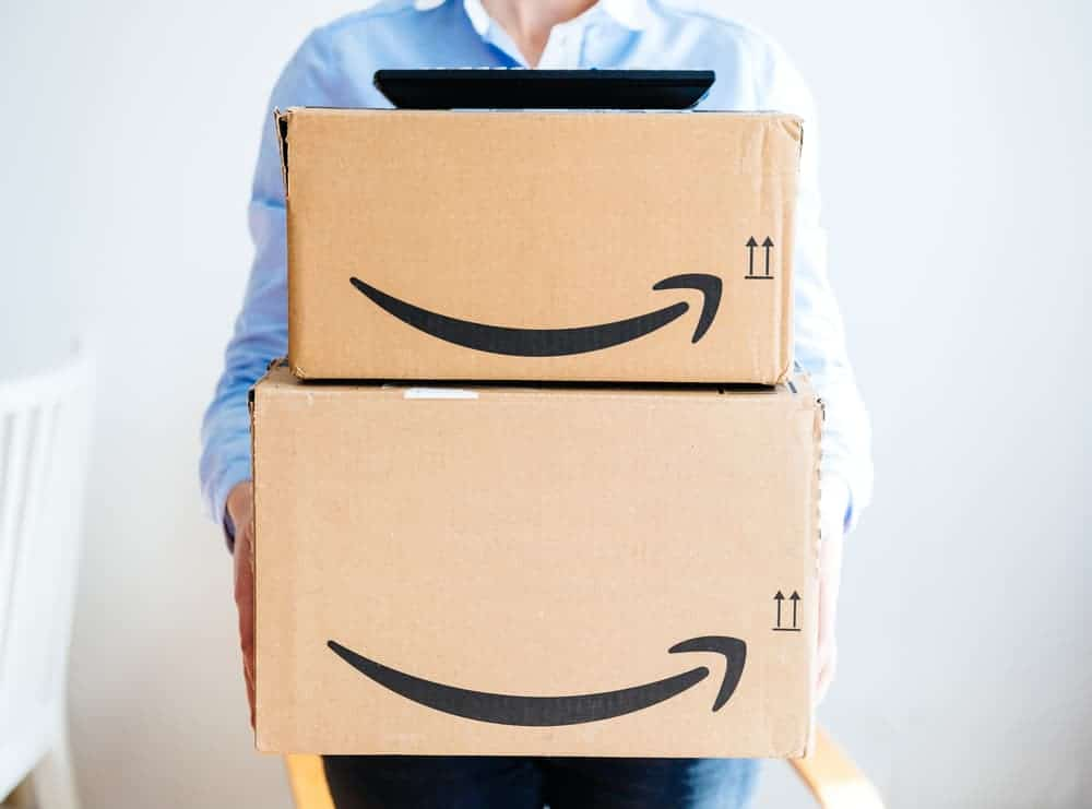 the front of happy smiling woman holding two large Amazon Prime cardboard boxing after delivery - TV set remote on top on boxes