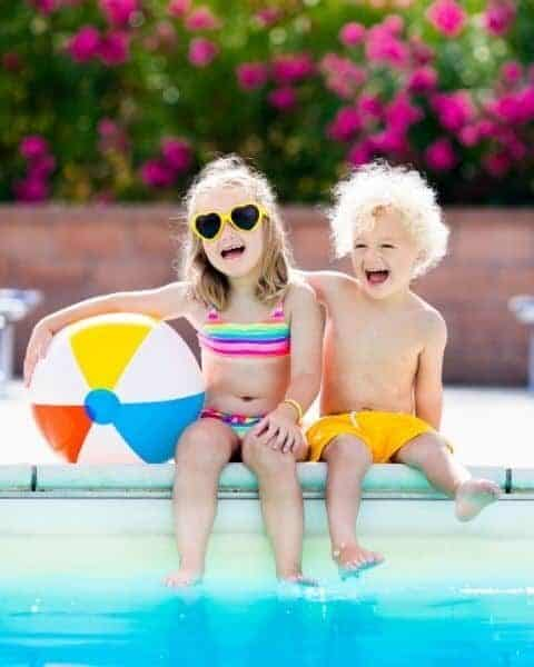 little boy and girl sitting by the pool with a beach ball