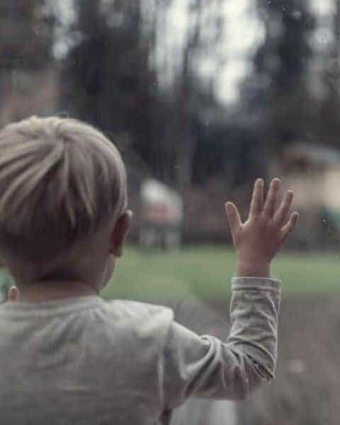 little boy standing near a window watching it rain outside