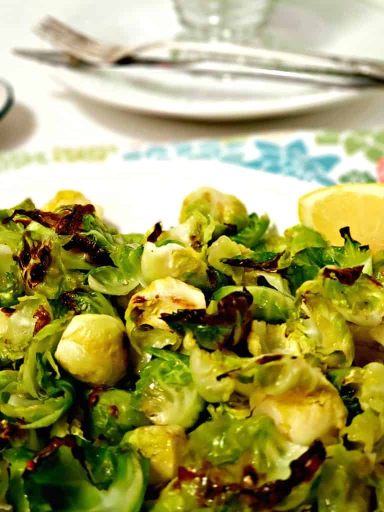 brussel sprouts on white plate with lemon