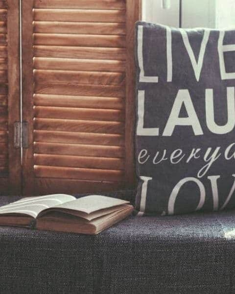 book sitting near a window with a pillow that says live, laugh love everyday