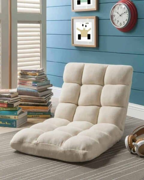 Soft foldable reclining chair in a corner with a stack of books.