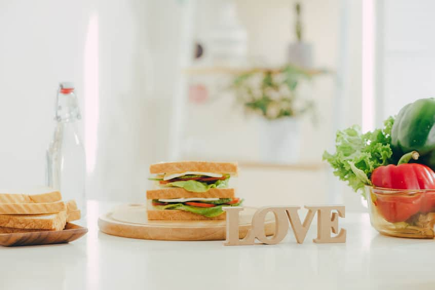 "A sandwich on a plate behind a sign that reads, ""love."""