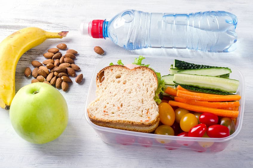A healthy school lunch, including fruits, vegetables, and water.
