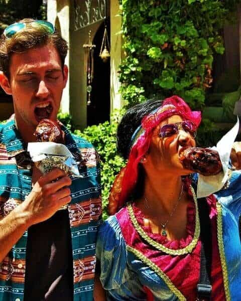 a man and a woman eating turkey legs at the Renaissance Festival